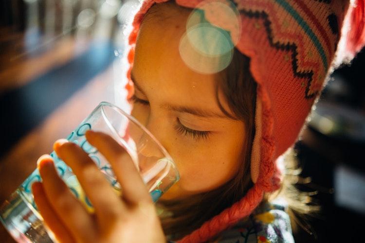 Fillette buvant l'eau dans un verre pour faire passer un hoquet