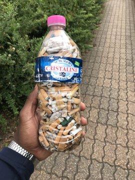 Un homme tenant une bouteille plastique remplie de mégots de cigarettes