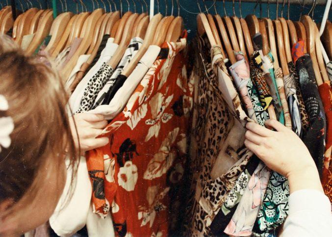Une femme fouillant parmi les robes vintage.