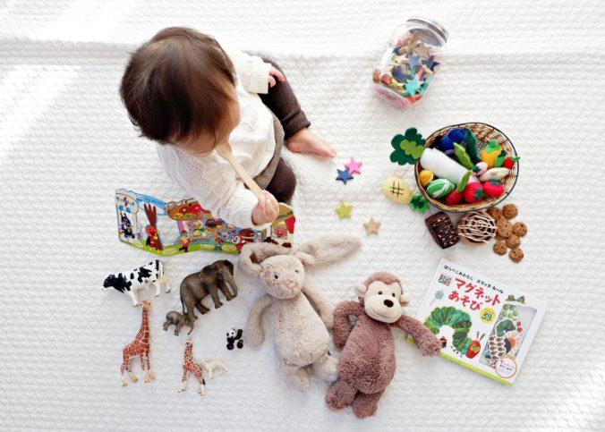 Un enfant au mileiu de ses jouets.